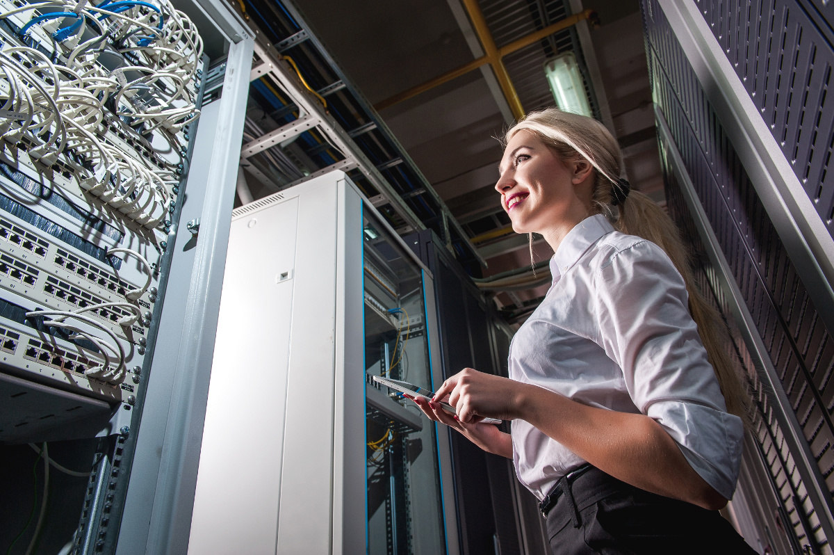 Smiling Female Technician with Tablet in Server Room